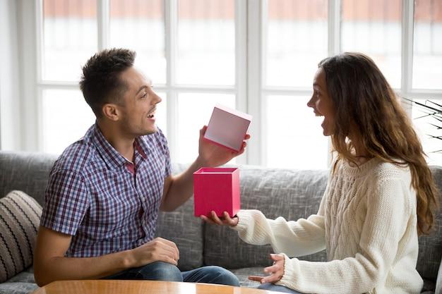 Opgewekte jonge mens het openen giftdoos die heden van vrouw ontvangt Gratis Foto