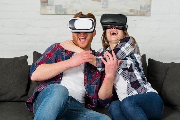 Opgewekte jonge paarzitting op bank die een vrhoofdtelefoon met behulp van en virtuele werkelijkheid ervaart Gratis Foto
