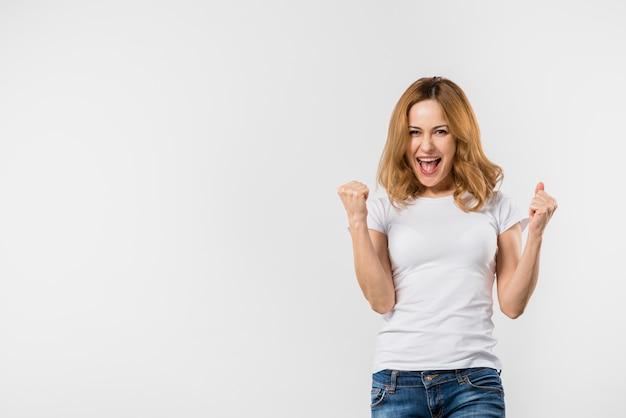 Opgewekte jonge vrouw die haar vuist balt tegen witte achtergrond Gratis Foto