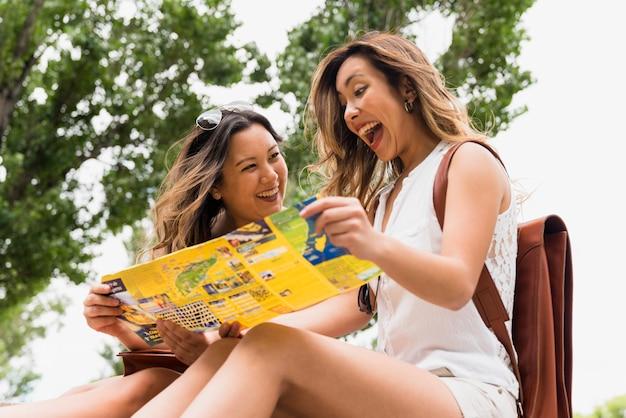 Opgewekte jonge vrouwelijke toeristenzitting onder de boom die kaart bekijken Gratis Foto