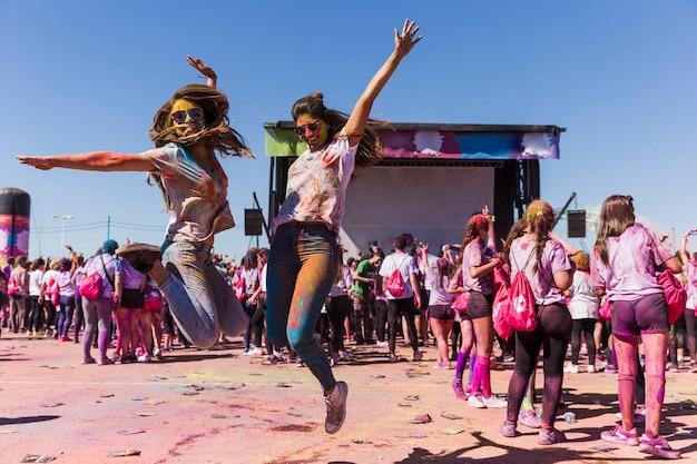 Opgewekte jonge vrouwen die in lucht springen die het holifestival vieren Gratis Foto