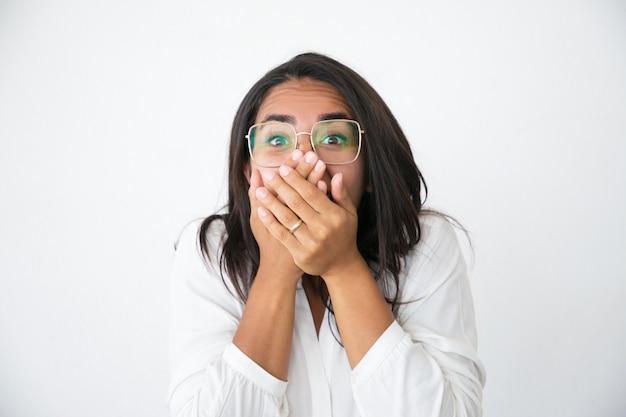 Opgewekte vrolijke vrouw in bril geschokt met nieuws Gratis Foto