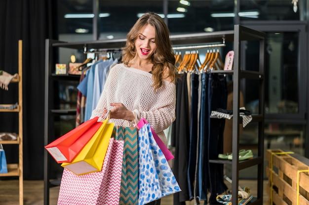 Opgewekte vrouw die binnen kleurrijke het winkelen zakken kijkt Gratis Foto