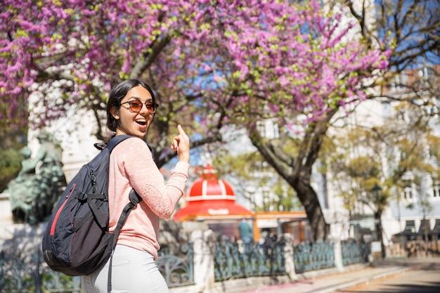 Opgewekte vrouw die rugzak draagt en op tot bloei komende boom richt Gratis Foto