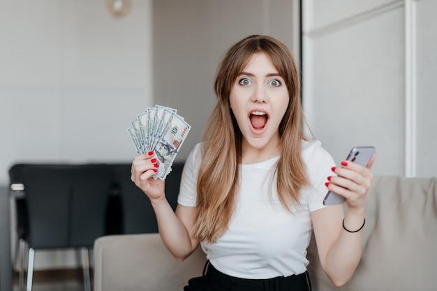 Opgewekte vrouw met het geld van dollarrekeningen en telefoon in hand zitting op laag thuis Premium Foto
