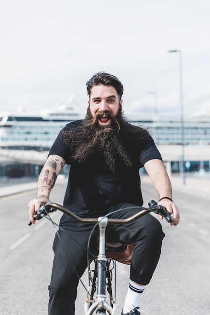Opgewonden bebaarde jonge man genieten van het berijden van de fiets Gratis Foto