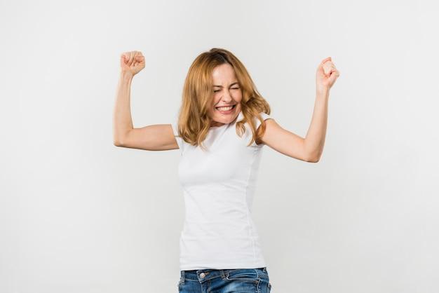 Opgewonden blonde jonge vrouw balde haar vuist tegen een witte achtergrond Gratis Foto