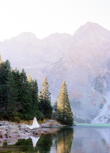 Opgewonden bruid staat omringd door schoonheid van het hooglandmeer en de bergen Gratis Foto