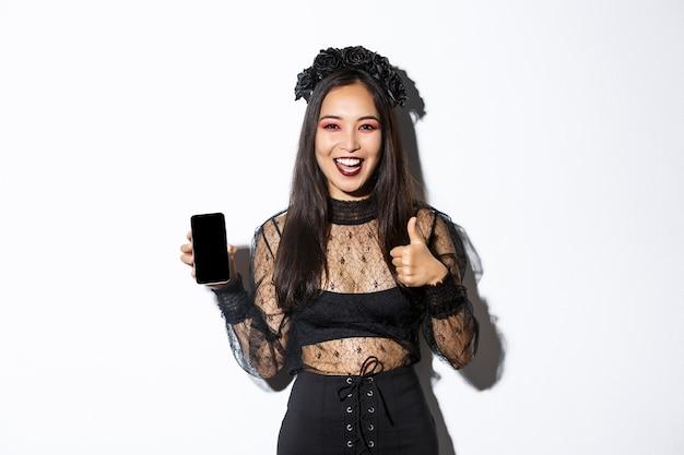 Opgewonden en tevreden aziatische vrouw in halloween-kostuum met thumbs-up in goedkeuring en demonstreren gsm-scherm, staande over witte muur Gratis Foto
