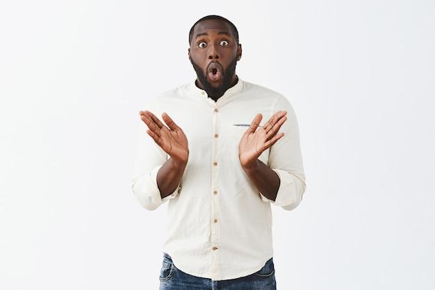 Opgewonden en verrast jonge kerel die zich voordeed tegen de witte muur Gratis Foto