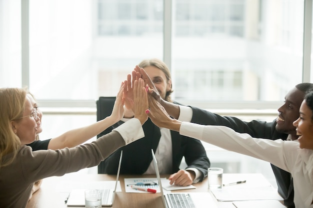 Opgewonden gelukkig multiraciaal commercieel team dat high-five geeft op kantoorvergadering Gratis Foto