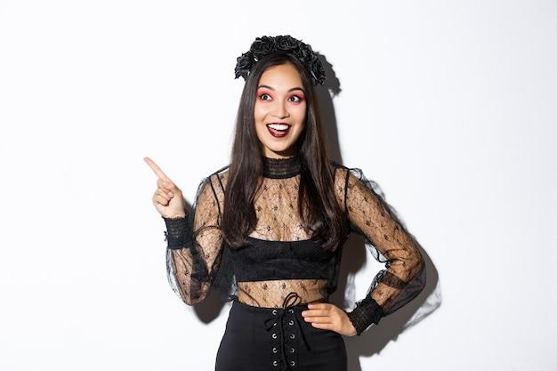 Opgewonden gelukkige aziatische vrouw in zwarte kanten jurk en krans kijkt verbaasd naar de linkerbovenhoek, wijzende vinger naar je halloween-promobanner, staande op een witte achtergrond. Gratis Foto