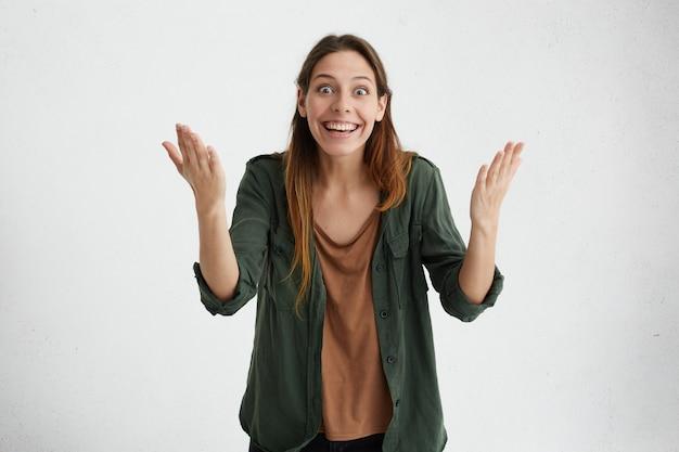 Opgewonden gelukkige vrouw die haar handen met opwinding opheft en haar triomf op de wedstrijd demonstreert. prachtig vrouwtje met brede glimlach tevreden met de overwinning Gratis Foto
