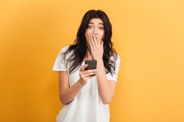Opgewonden geschokt jonge mooie vrouw chatten via de mobiele telefoon. Premium Foto