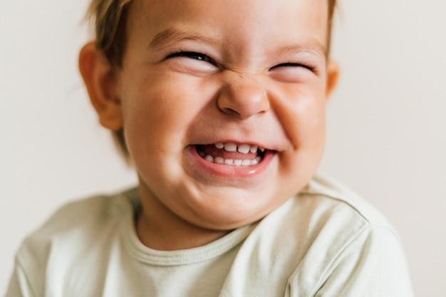 Opgewonden gezicht van een kleine baby peuter op witte achtergrond Premium Foto