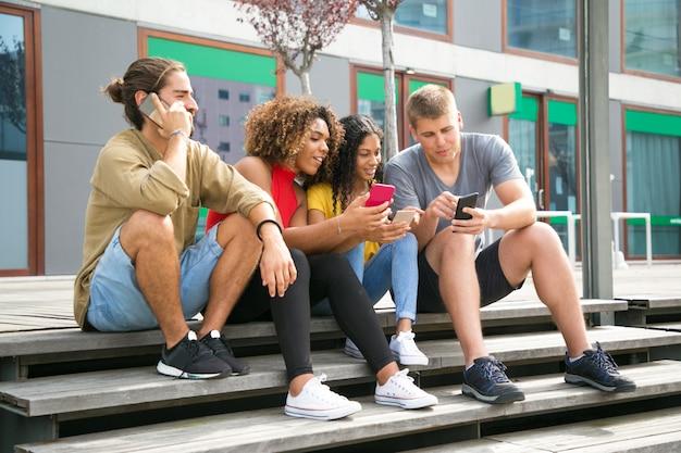 Opgewonden groep vrienden met behulp van de mobiele telefoon Gratis Foto