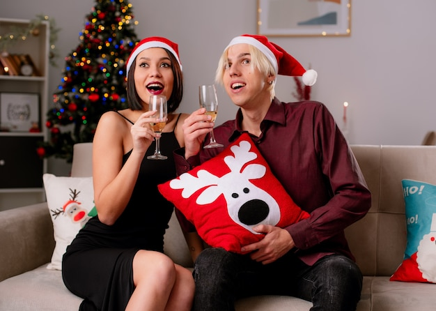 Opgewonden jong koppel thuis in de kersttijd met kerstmuts zittend op de bank in de woonkamer Gratis Foto