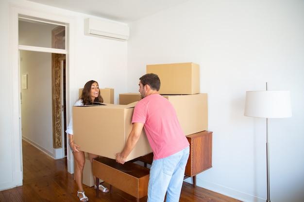 Opgewonden jong koppel verhuizen naar nieuwe flat, kartonnen dozen zorgvuldig dragen Gratis Foto