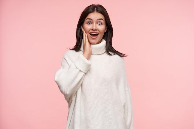 Opgewonden jonge aantrekkelijke bruinharige vrouw met casual kapsel die emotionele hand naar haar gezicht opheft terwijl ze verrast naar voren kijkt, geïsoleerd over roze muur Gratis Foto