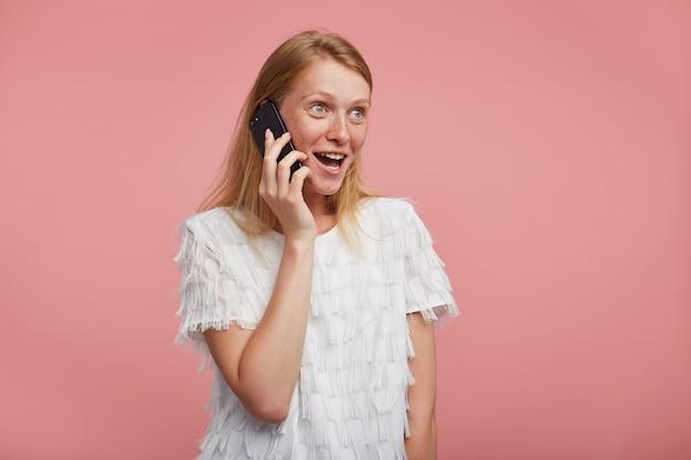 Opgewonden jonge aantrekkelijke vrouw met natuurlijke make-up kijkt vreugdevol vooruit met opgewonden gezicht terwijl ze haar vriend belt, staande tegen een roze achtergrond Gratis Foto