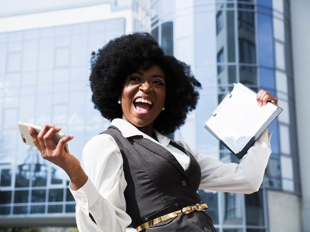 Opgewonden jonge afrikaanse zakenvrouw bedrijf mobiele telefoon en klembord Gratis Foto
