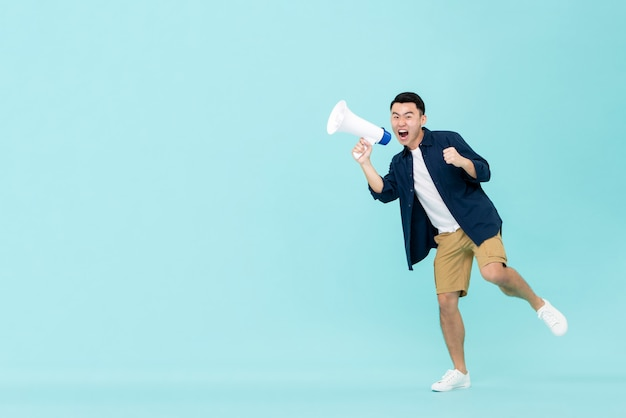 Opgewonden jonge aziatische man met megafoon en schreeuwen Premium Foto