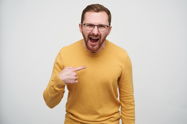 Opgewonden jonge bruinharige man met baard met kort kapsel en het dragen van een casual pullover terwijl hij staat, emotioneel schreeuwt en zichzelf laat zien Gratis Foto