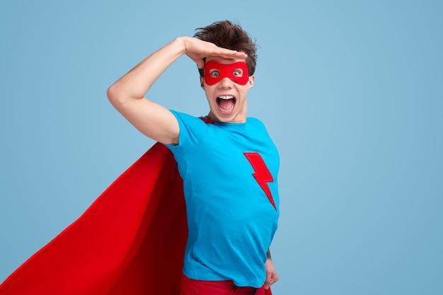 Opgewonden jonge man in superheld kostuum hand in de buurt van voorhoofd te houden en camera met geopende mond tegen blauwe achtergrond te kijken Premium Foto