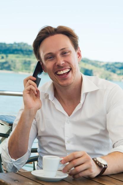 Opgewonden jonge man lachen terwijl praten over de telefoon Gratis Foto