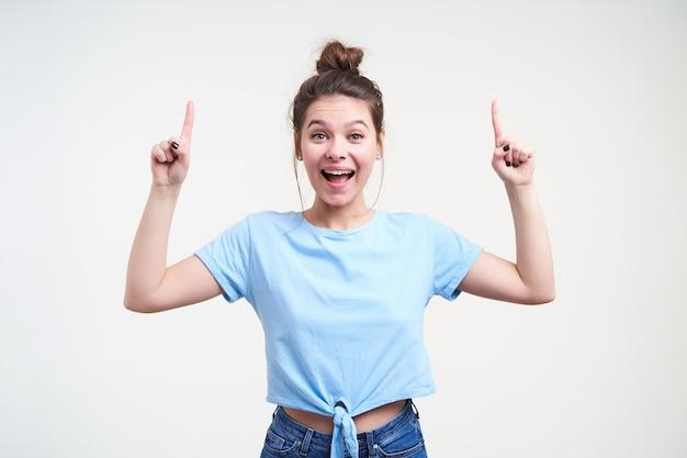 Opgewonden jonge mooie bruinharige vrouw met natuurlijke make-up camera kijken met grote ogen en mond geopend terwijl naar boven wijzend met wijsvingers, geïsoleerd op witte achtergrond Gratis Foto