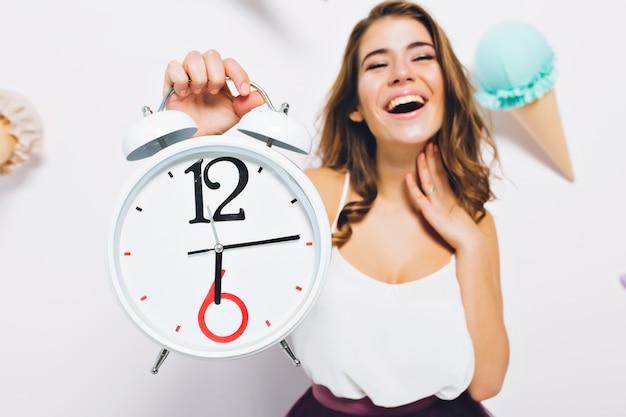 Opgewonden jonge vrouw met grote klok in de hand te wachten op verjaardagsfeestje begint staan op versierde muur. close-upportret van vrolijk meisje verheugt zich aan het eind van de werkdag. Gratis Foto