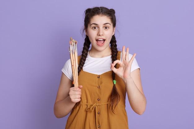 Opgewonden jonge vrouw met schilderen geborsteld in handen, ok teken tonen en schreeuwen Gratis Foto