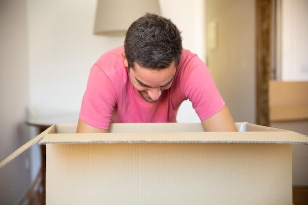 Opgewonden jongeman dingen uitpakken in zijn nieuwe appartement, kartonnen doos openen, Gratis Foto