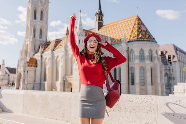 Opgewonden kaukasisch meisje in glamoureuze outfit emotioneel poseren in de buurt van oud mooi paleis Gratis Foto