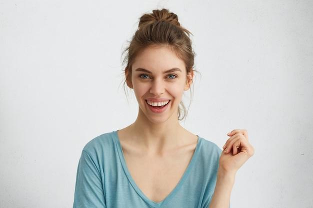 Opgewonden lachende jonge vrouw met haarknoop positieve emoties uiten tijdens het poseren Gratis Foto