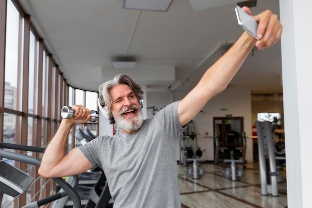 Opgewonden man selfies nemen op sportschool Gratis Foto