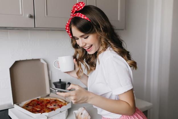 Opgewonden meisje met lint in haar koffie drinken in de ochtend. binnen schot van innemende dame die pizza eet tijdens het ontbijt. Gratis Foto