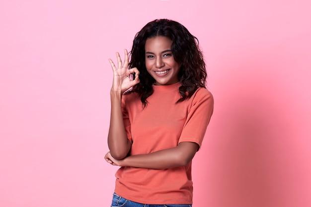 Opgewonden mooie afrikaanse vrouw met ok gebaar, gekleed in casual roze t-shirt geïsoleerd op roze muur. Premium Foto