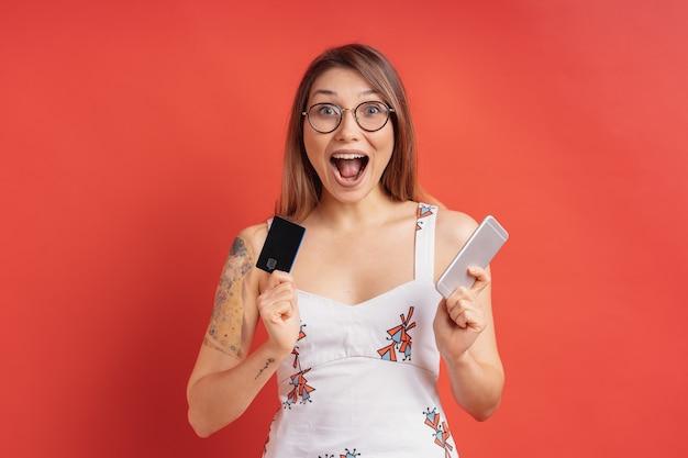 Opgewonden mooie jonge vrouw met telefoon en creditcard in haar handen Gratis Foto