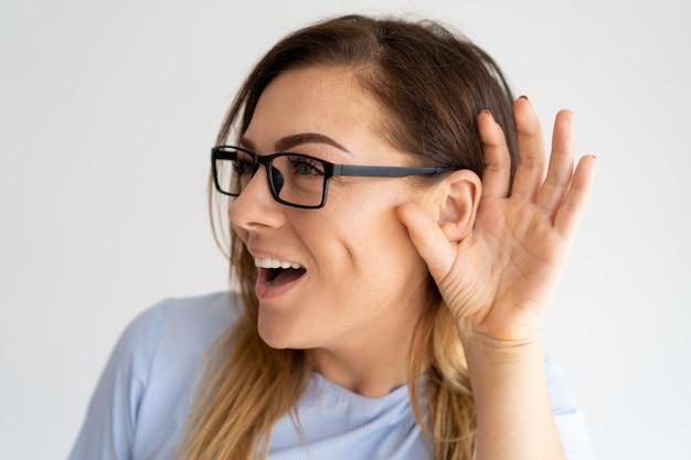Opgewonden mooie vrouw die hand in de buurt van oor Gratis Foto