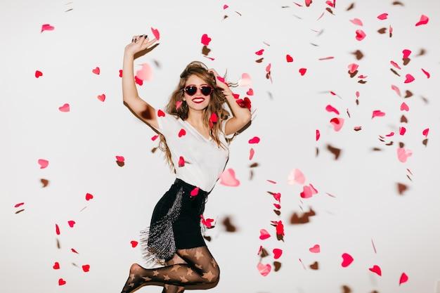 Opgewonden op blote voeten vrouw die onder hartconfettien springt Gratis Foto