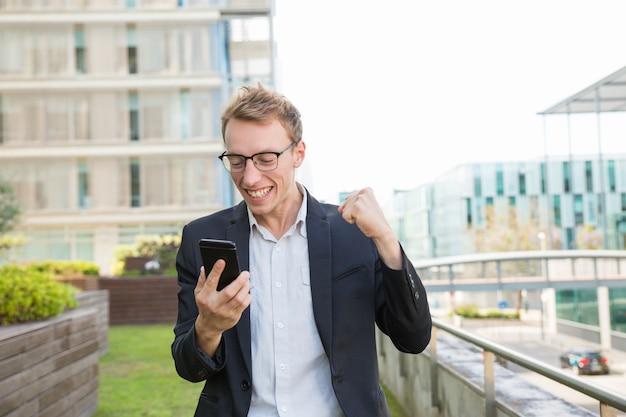 Opgewonden positieve man die bericht ontvangt Gratis Foto