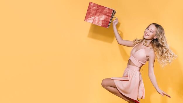 Opgewonden springende vrouw met boodschappentassen Gratis Foto