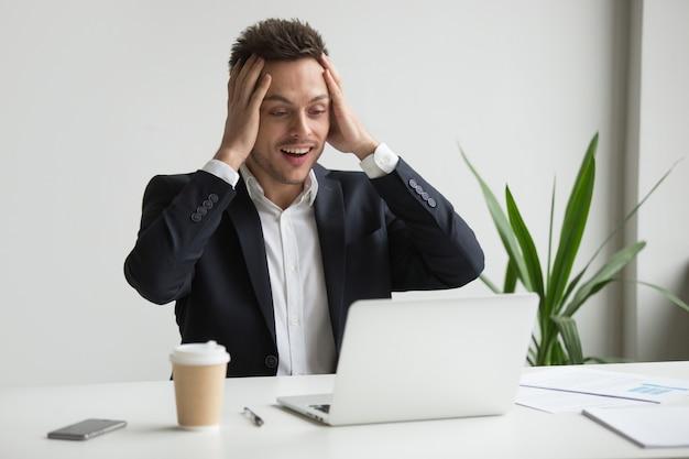 Opgewonden verbaasd millennial zakenman verrast door onverwacht goed nieuws online Gratis Foto