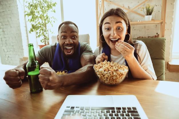 Opgewonden voetbalfans die thuis naar sportwedstrijden kijken, ondersteuning op afstand van hun favoriete team tijdens een pandemie van het coronavirus Gratis Foto