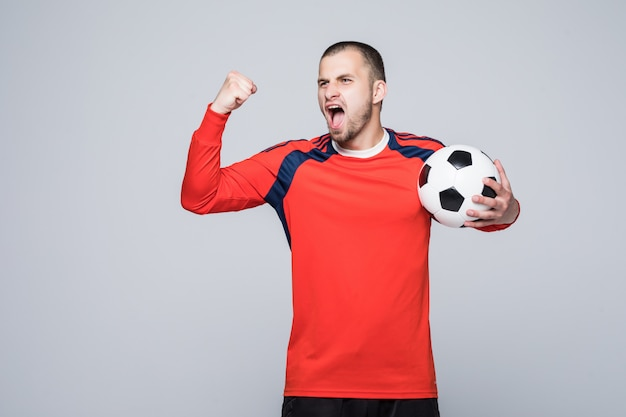 Opgewonden voetballer die in rood t-shirt een concept van de voetbaloverwinning houdt dat op wit wordt geïsoleerd Gratis Foto