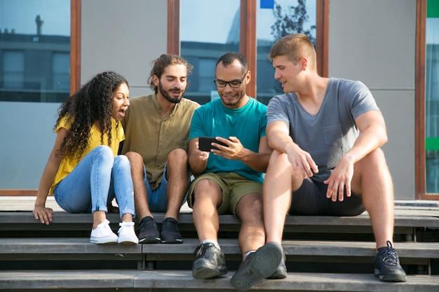 Opgewonden vrienden kijken naar video op mobiele telefoon Gratis Foto