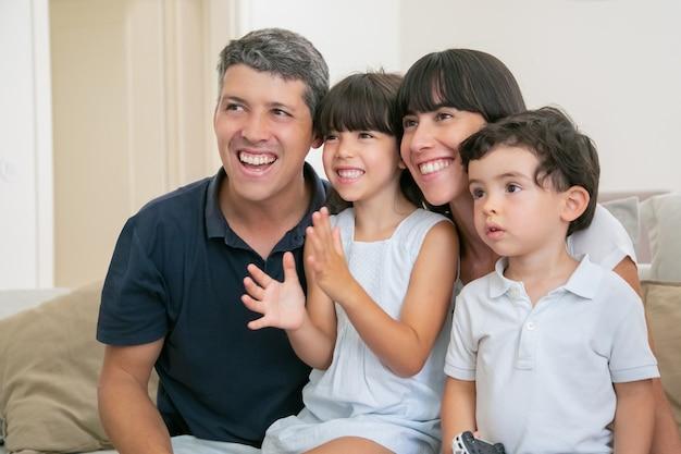 Opgewonden vrolijk ouderpaar met twee kinderen tv kijken, zittend op de bank in de woonkamer, wegkijken en glimlachen. Gratis Foto