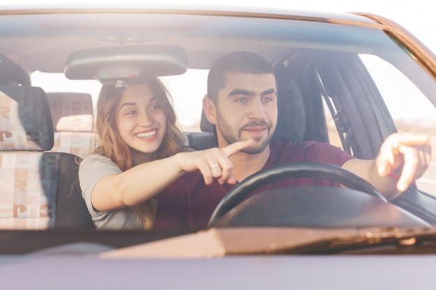 Opgewonden vrouw en man in de auto Gratis Foto