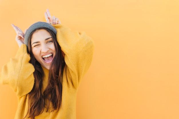 Opgewonden vrouw hoorn gebaar tonen tegen geel oppervlak Gratis Foto